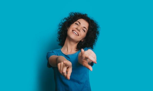 Close up ritratto di una bella donna riccia ridendo e indicando la telecamera vestita di blu agastin uno sfondo blu studio.
