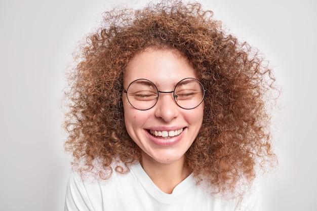 Close up ritratto di bella modella femminile dai capelli ricci ride felicemente tiene gli occhi chiusi indossa occhiali trasparenti rotondi maglietta casual isolata sul muro bianco ridacchia sta spensierata