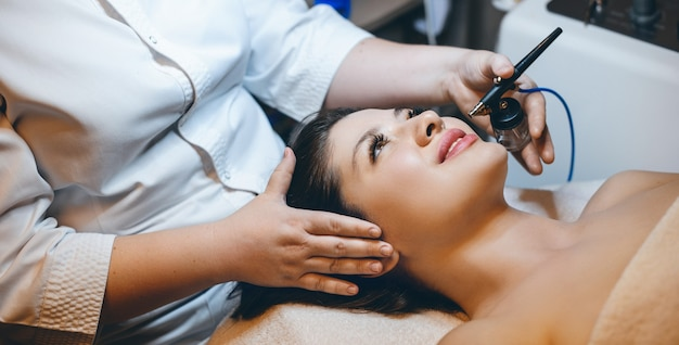 Chiuda sul ritratto di una donna adorabile che fa una terapia di ossigeno sul viso mentre si appoggia con gli occhi chiusi su un letto termale in una località termale.