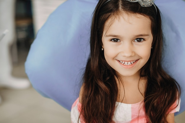 Chiuda sul ritratto di una bambina adorabile che ride guardando la fotocamera mentre è seduto su un sedile per stomatologia.
