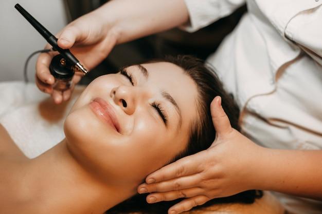 Chiuda sul ritratto di una donna adorabile che si appoggia su un letto della stazione termale con gli occhi chiusi che sorride mentre avendo ossigenoterapia sul suo fronte in un centro benessere.