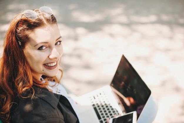 Close up ritratto di una bella giovane donna plus size con i capelli rossi che lavora al suo laptop mentre era seduto nel parco guardando la telecamera sopra la spalla sorridente.