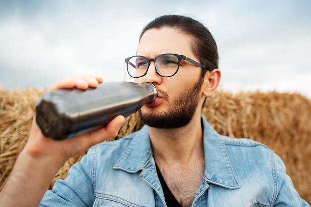 Ritratto del primo piano dell'uomo che beve acqua da una bottiglia ecologica in acciaio vicino a mucchi di fieno.