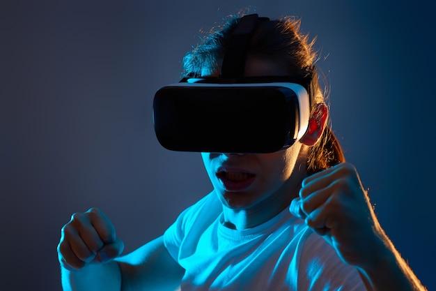 Ritratto del primo piano dell'uomo che usa gli occhiali della realtà virtuale su sfondo blu scuro. luce al neon.