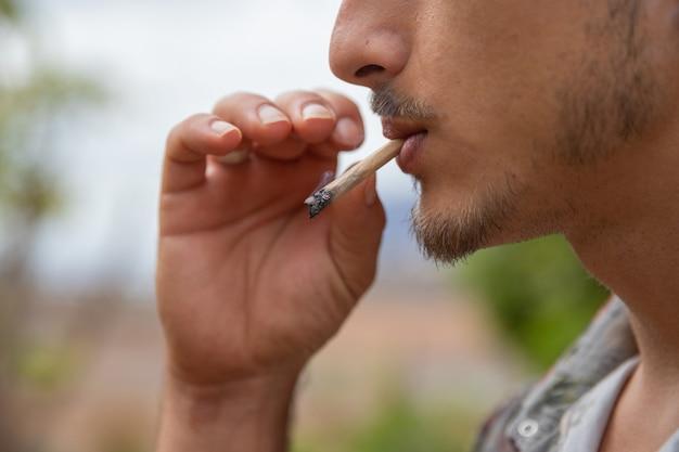 Chiuda sul ritratto di un uomo che fuma uno spinello di marijuana