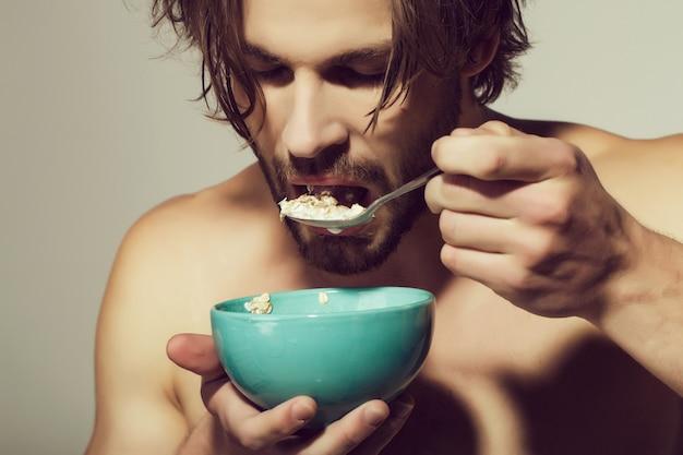 Close up ritratto di uomo con cucchiaio. cereali per la colazione, cibo sano per uomo o atleta sportivo su sfondo grigio.