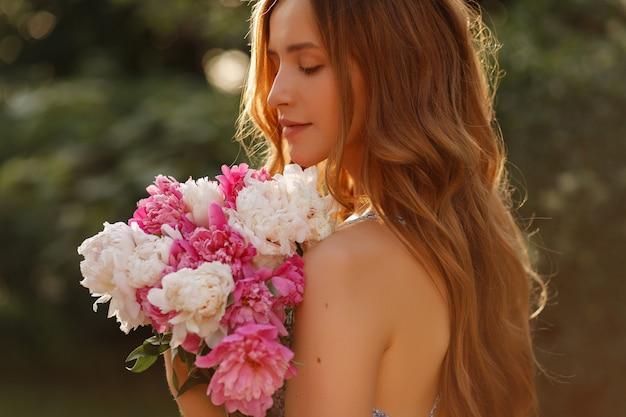 Ritratto del primo piano di un modello con i fiori di estate. passeggiare nel parco in primavera. sfondo sfocato
