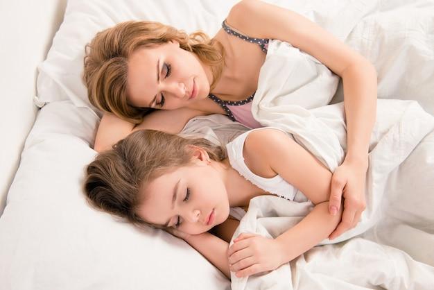 Chiuda sul ritratto di mamma e figlia che dormono adorabile nel letto