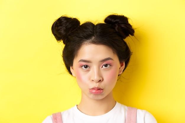 Chiuda sul ritratto della ragazza asiatica lunatica imbronciato e guardando sconvolto alla telecamera, in piedi con trucco glamour e hairbuns su giallo