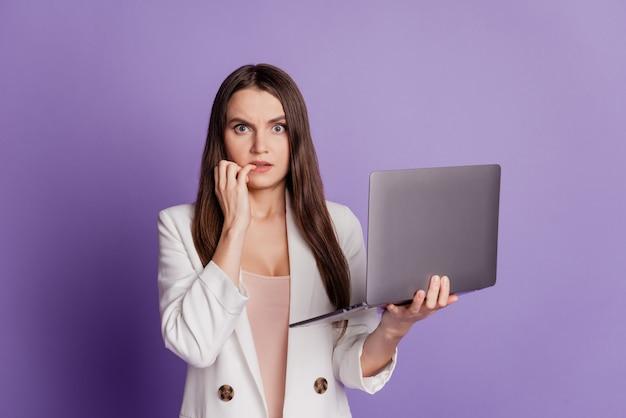 Ritratto ravvicinato di una signora pazza nervosa che tiene le dita del morso del netbook sul muro viola