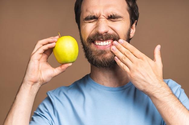 Close up ritratto di nervoso infelice turbato bell'uomo barbuto che tocca la sua guancia ha mal di denti isolato su sfondo beige copyspace.