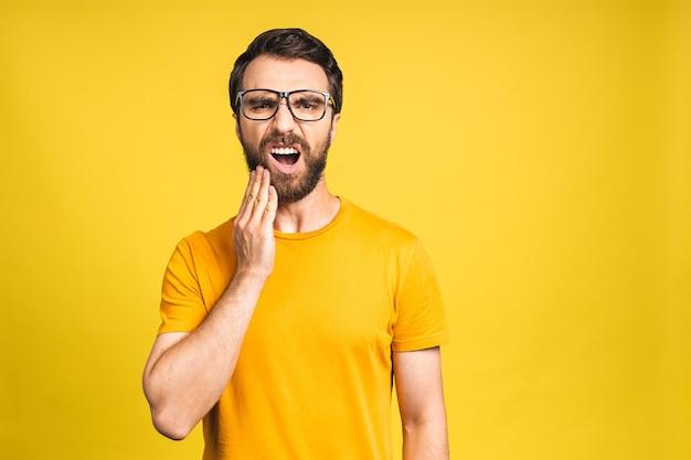 Close up ritratto di nervoso infelice turbato bell'uomo barbuto che tocca la sua guancia ha mal di denti isolato su sfondo giallo copyspace.