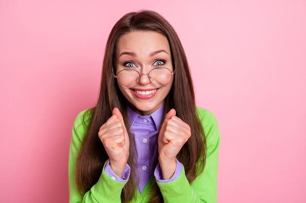 Ritratto ravvicinato di una bella ragazza allegra allegra e felice, geek in attesa di grandi notizie isolate su uno sfondo di colore rosa pastello