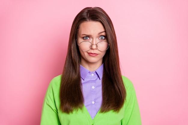 Close-up ritratto di bella attraente dubbiosa scettica ragazza dai capelli castani che ti guarda isolata su sfondo rosa color pastello