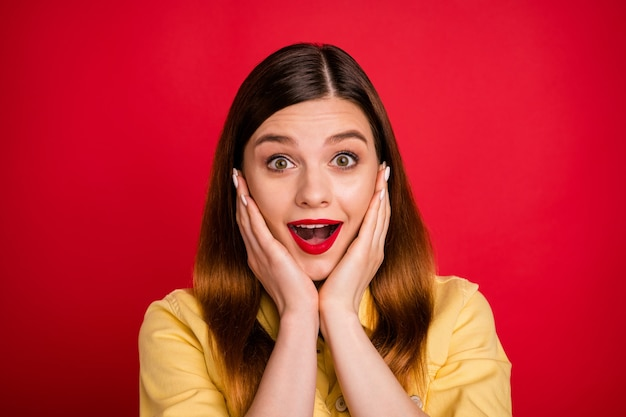 Ritratto del primo piano di bella attraente bella piuttosto carina stupita felice allegra allegra ragazza dai capelli rossi buona notizia reazione isolata su brillante vivido brillantezza vibrante sfondo di colore rosso