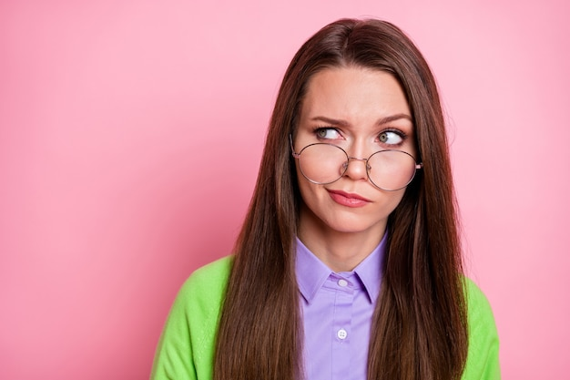 Ritratto ravvicinato di una bella ragazza dai capelli lunghi dubbiosa scettica esitante che guarda da parte sospettosamente isolata su sfondo rosa color pastello
