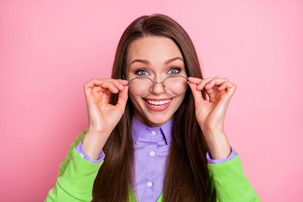 Close-up ritratto di bella bella cervellona allegra ragazza dai capelli lunghi nerd geek toccando le specifiche isolate su sfondo rosa color pastello