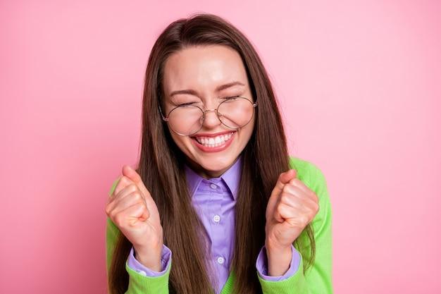 Close-up ritratto di bella piuttosto allegra allegra gioiosa ragazza geek che tiene i pugni godendo isolato su sfondo rosa color pastello