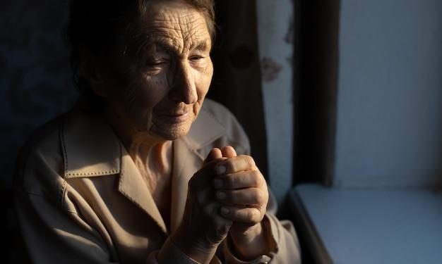Ritratto ravvicinato di una donna anziana che prega