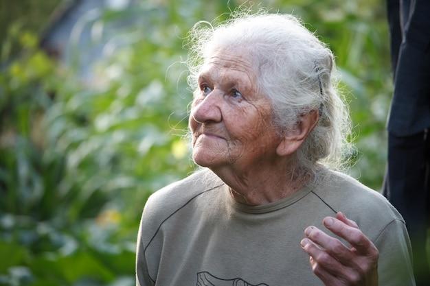 Ritratto del primo piano di una donna anziana con capelli grigi che sorride e che cerca, fronte nelle rughe profonde