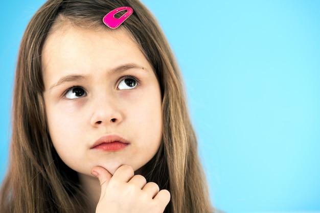 Chiuda sul ritratto della bambina sveglia pensierosa con la forcina rosa su fondo blu. concetto di sogni infantili.