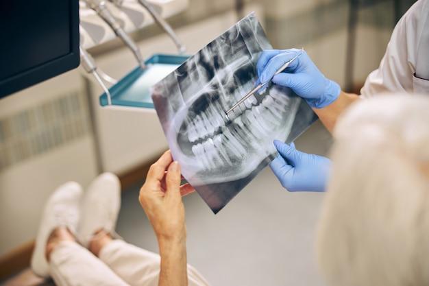 Primo piano ritratto della foto del cliente dei denti mentre si parla con il medico ortodontista in clinica dentale