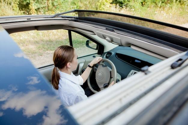 Primo piano ritratto di una donna dall'aspetto piacevole con felice espressione positiva, soddisfatto del viaggio indimenticabile in auto, si siede sul sedile del conducente. persone, guida, concetto di trasporto