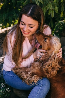 Ritratto del primo piano della ragazza soddisfatta con il cane che abbraccia i capelli lunghi con gli occhi chiusi. giovane donna sorridente che gode della buona giornata e posa con l'animale domestico sul cortile