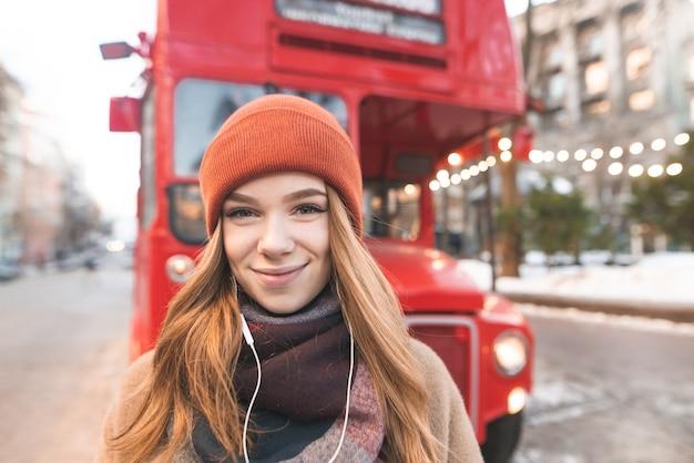 Il ritratto del primo piano di una ragazza positiva in cuffie esamina la macchina fotografica sul retro di un autobus rosso