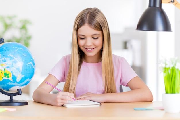 Ritratto ravvicinato di una ragazzina positiva che studia in remoto la scrivania del tavolo scrivi a matita il libro copia il progetto della scuola primaria in casa al chiuso
