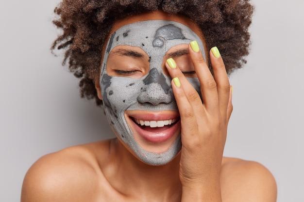 Il ritratto ravvicinato di una donna positiva tiene gli occhi chiusi sorride ampiamente tiene la mano sul viso applica la maschera di argilla