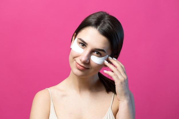 Ritratto ravvicinato di una ragazza piuttosto attraente con le spalle nude che usa i cerotti sotto gli occhi