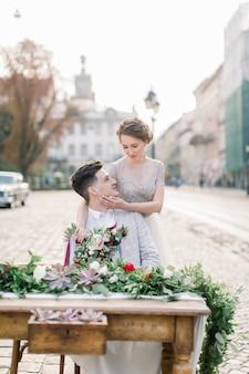 Ritratto del primo piano della sposa graziosa e dello sposo bello, abbracciando e sedendosi alla tavola decorata, fondo della vecchia città