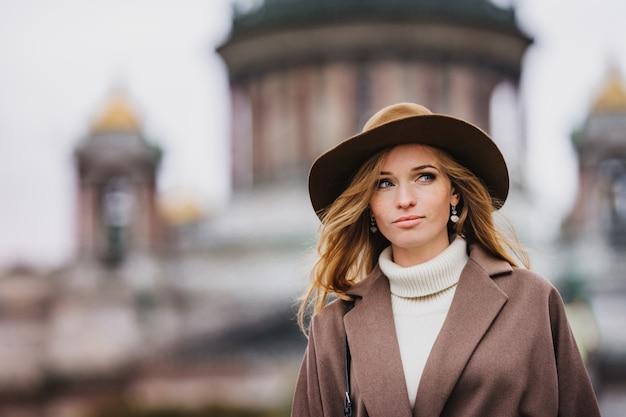 Chiuda sul ritratto di una donna dai capelli rossi graziosa che porta il cappotto beige