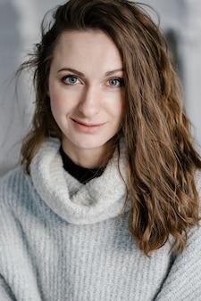 Ritratto del primo piano di una giovane donna abbastanza sorridente in maglione accogliente che guarda direttamente