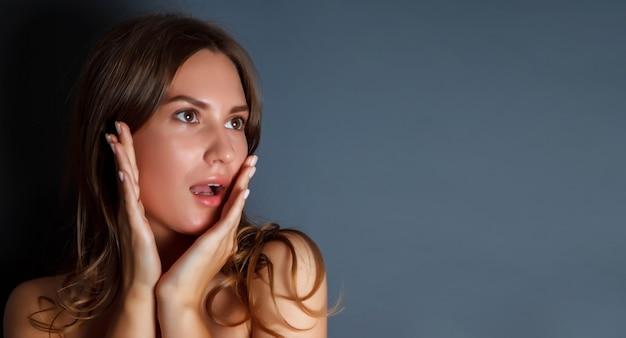 Ritratto ravvicinato di una bella giovane donna spaventata con le mani sul viso su sfondo scuro isolato Foto Premium