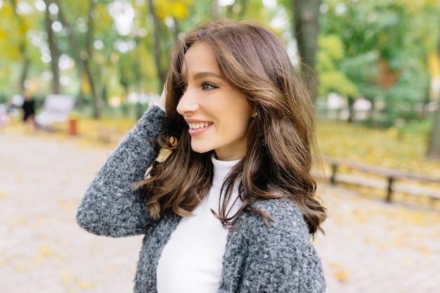 Close up ritratto di profilo di donna sensibile. ha i capelli corti e scuri e meravigliosi grandi occhi azzurri. nel parco verde.