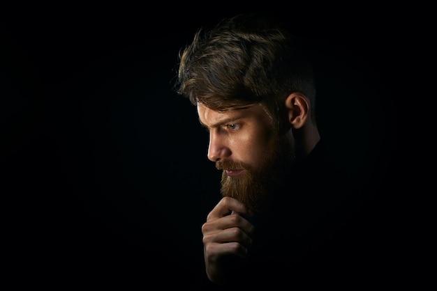 Ritratto ravvicinato di un giovane perplesso che tocca la barba guardando in basso su sfondo nero
