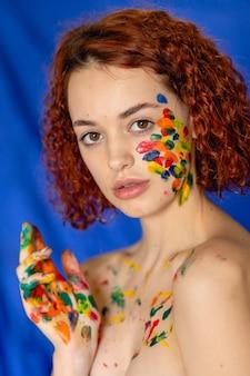 Close-up ritratto di donna dai capelli ricci rossa giovane allegro sporco di vernice. ritratto di una ragazza con un motivo creativo sul viso. fotografia concettuale per l'arte o blog di donne