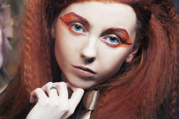 Chiuda sulla donna del redhair del ritratto con trucco creativo luminoso