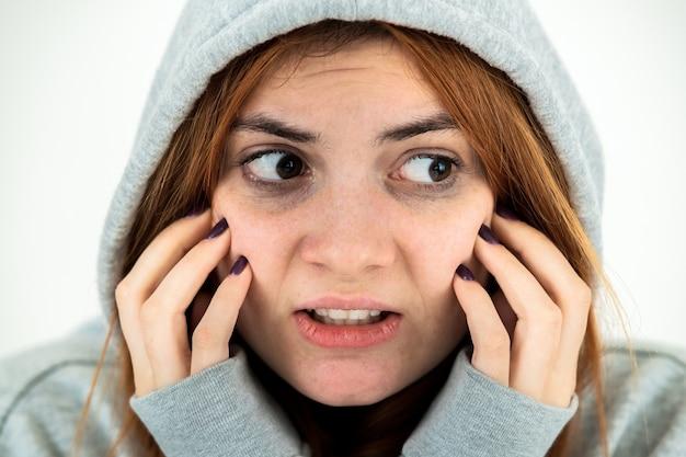 Close up ritratto di paura giovane donna rossa che indossa felpa con cappuccio