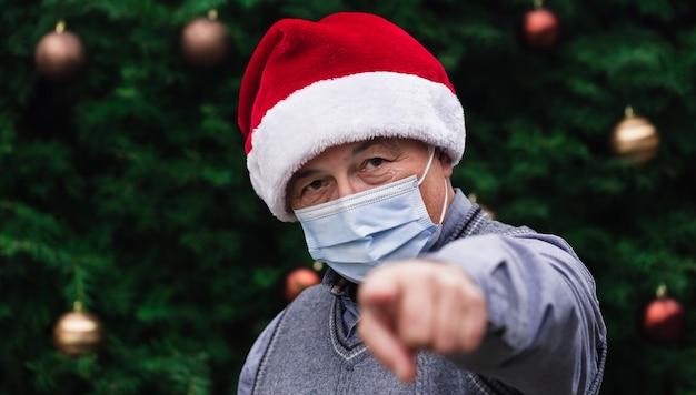 Close up ritratto di uomo anziano che indossa un cappello di babbo natale e mascherina medica con emozione e mostra il dito. sullo sfondo di un albero di natale. pandemia di coronavirus