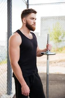 Ritratto ravvicinato di un serio sportivo barbuto che tiene il bilanciere in piedi all'aperto