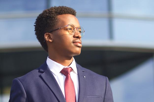 Close up ritratto di serio fiducioso imprenditore di successo in giacca e cravatta, occhiali. giovane afroamericano africano nero che esamina la distanza con sguardo intelligente intelligente. affari, concetto di successo