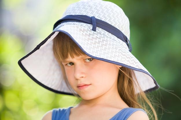 Ritratto del primo piano della bambina seria in un grande cappello. bambino che si diverte tempo all'aperto in estate.
