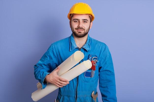 Chiuda sul ritratto dell'uomo serio che indossa l'uniforme e il casco, attraente architetto considera disegni isolati su sfondo blu, giovane caposquadra guardando direttamente la fotocamera, funziona con il nuovo progetto.