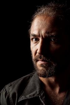 Chiuda sul ritratto di un uomo barbuto di mezza età pensieroso serio nel buio