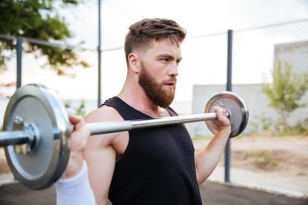 Ritratto ravvicinato di un giovane atleta serio in piedi e che tiene il bilanciere all'aperto