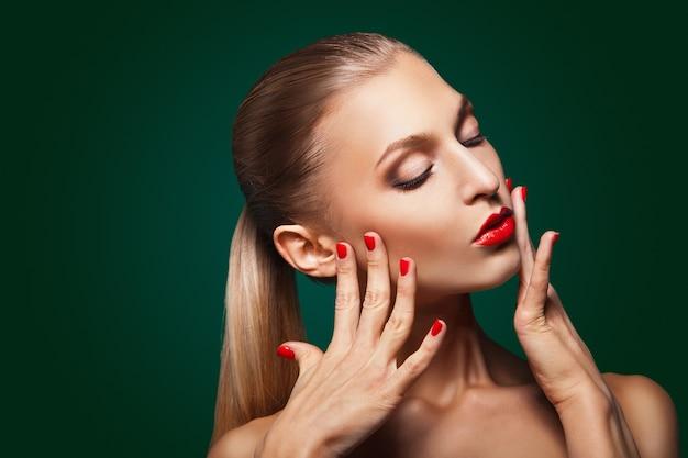 Ritratto ravvicinato di una giovane donna caucasica sexy con trucco glamour rosso e manicure brillante su sfondo verde