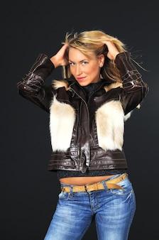 Ritratto del primo piano di una giovane donna misteriosa sexy in una giacca mezza stagione e jeans su un nero
